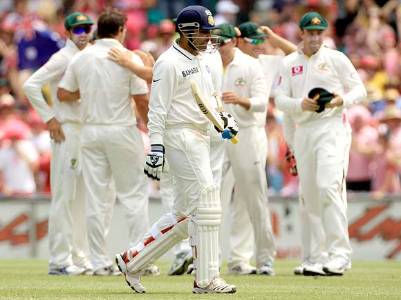 Virender Sehwag walks back after his dismissal