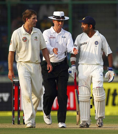 Umpire Billy Bowden (centre) separates a confrontation between Simon Katich (left) of Australia and Gautam Gambhir