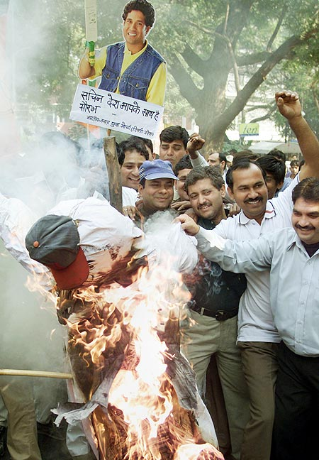 Supporters burn an effigy of match referee Mike Denness, as others hold a poster of national cricket icon Sachin