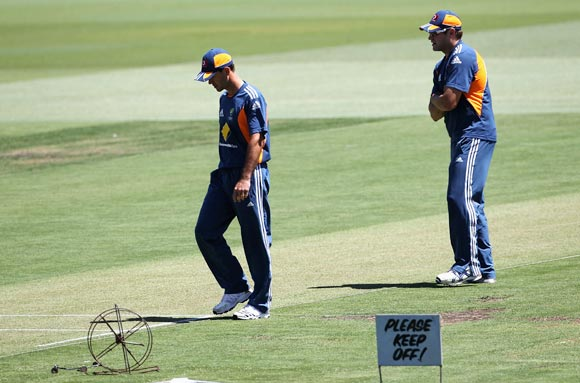 Ricky Ponting (left) and Ryan Harris check the pitch