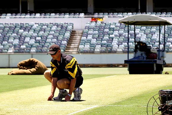 Curator Cameron Sutherland inspects the pitch at the WACA cricket stadium in Perth