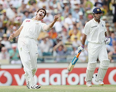 Mitchell Starc (left) of Australia celebrates after taking the wicket of Vinay Kumar
