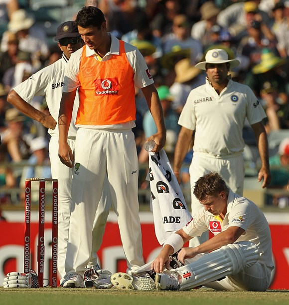 Warner regains his composure after being hit by a bouncer from Umesh Yadav