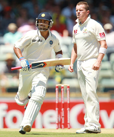 Virat Kohli of India runs past Peter Siddle of Australia during day three of the Third Test match between Australia and India at the WACA