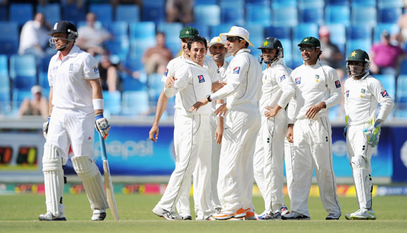Saeed Ajmal of Pakistan celebrates with teammates after dismissing Ian Bell (L) of England during the first Test match