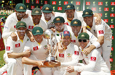 The Australian team pose with the Border-Gavaskar Trophy