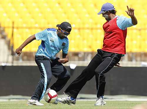 Sri Lanka's captain Mahela Jayawardene (L) and Sachithra Senanayake play football during a practice session