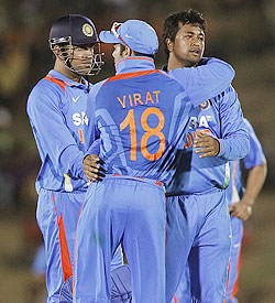 India's Pragyan Ojha (right) celebrates with captain Mahendra Singh Dhoni (left) and vice captain Virat Kohli after taking the wicket