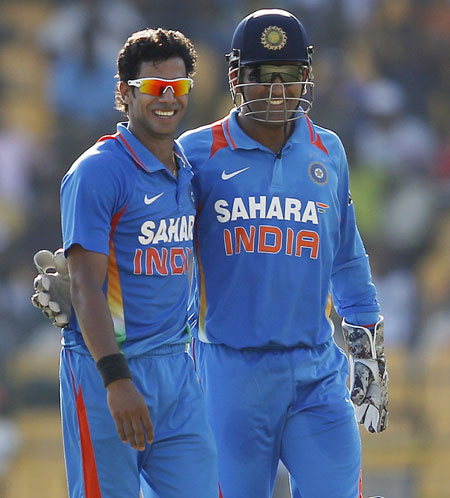 India's Manoj Tiwary (L) and captain Mahendra Singh Dhoni celebrate after taking the wicket of Sri Lanka's Dinesh Chandimal
