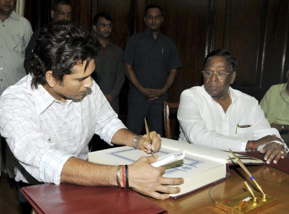 Sachin Tendulkar (left) signs the oath book as India's Minister of State for Parliamentary Affairs V Narayanasamy watches during the swearing-in ceremony