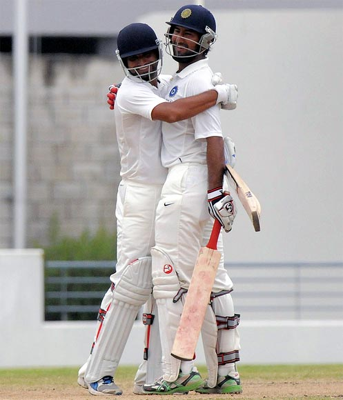 Cheteshwar Pujara (right) and Shami Ahmed celebrate winning the match