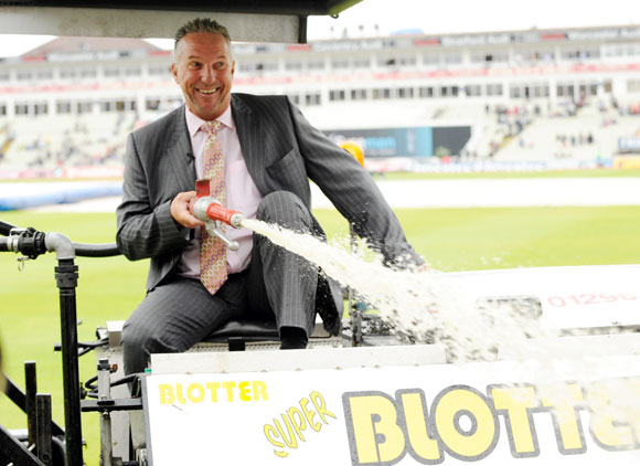 Former England player and Sky commentator Sir Ian Botham sprays water from a blotter as rain delayed the start of the third day of the third Ashes cricket test match in August 2009