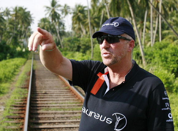 Former England cricket player Ian Botham gestures next to the train tracks as he talks about the train that was pushed off the tracks by the December 2004 tsunami