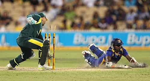 Matthew Wade of Australia breaks the stumps as Chamara Kapugedera puts in the dive during their match in Adelaide
