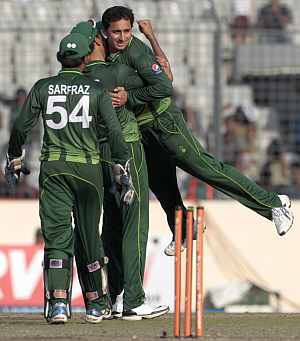 Ajmal is congratulated by teammates after dismissing Farveez Mahroof