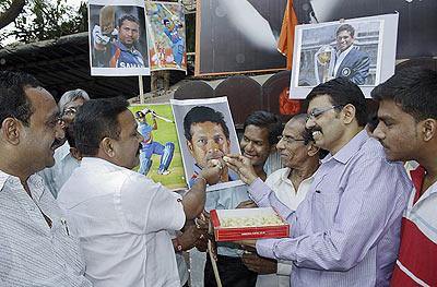 Fans Sachin Tendulkar celebrate his 100th international century on the outskirts of Mumbai on Friday