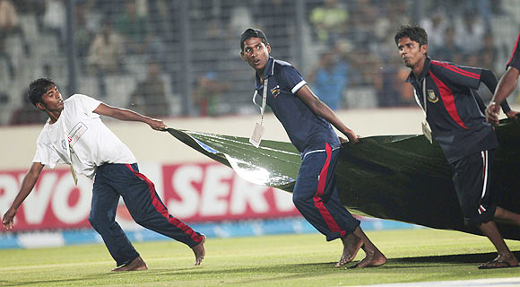 Groundsmen pull a cover sheet as rain interrupt the Asia Cup One Day International match