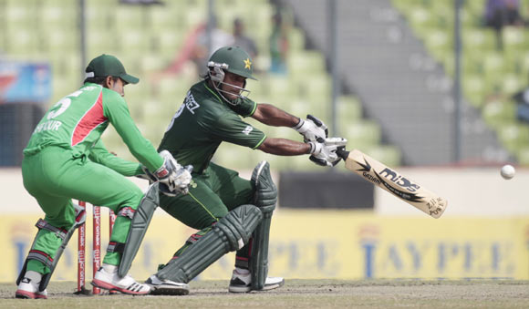 Pakistan's Mohammad Hafeez (R) plays a shot as Bangladesh's captain and wicket keeper Mushfiqur Rahim (L) looks on