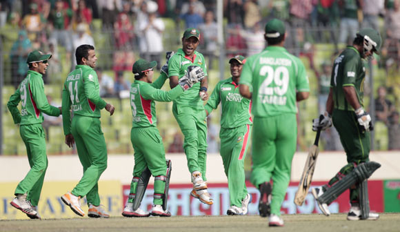 Pakistan's Mohammad Hafeez (R) leaves the field as Bangladesh's fielders celebrate his dismissal
