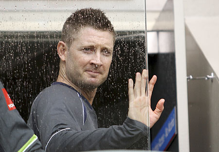 Australia's Michael Clarke looks out through a glass as it rains on the second day of the first Test against South Africa at the Gabba in Brisbane on Saturday