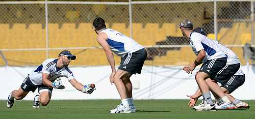 Wicketkeeper Matt Prior (L) of England goes for a catch during a slip fielding drill in a nets session at Sardar Patel Stadium