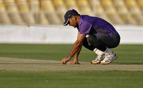 India's captain Mahendra Singh Dhoni inspects the pitch during a cricket practice session