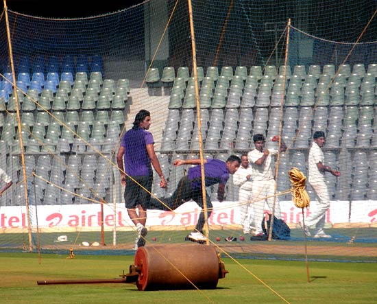 India captain MS Dhoni rolls his arm at the nets as Ishant Sharma watches