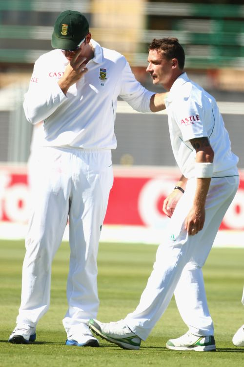 Graeme Smith of South Africa speaks to Dale Steyn of South Africa as he stretches his hamstring