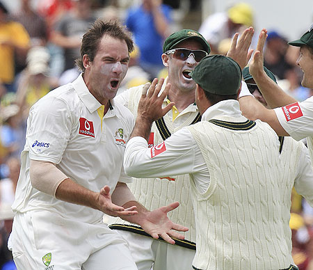 Australia's John Hastings (left) celebrates with teammates after picking his first Test wicket on dismissing South Africa's AB de Villiers on Day 1 of the third Test at the WACA