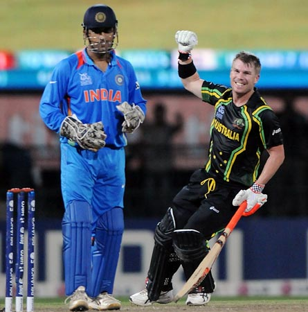 India captain Mahendra Singh Dhoni looks on as Australia's David Warner