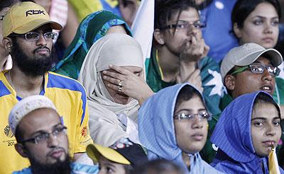 Pakistan fans wear a dejected look after the team's loss to Sri Lanka