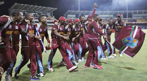 West Indies' Marlon Samuels waves a flag as his teammates watch