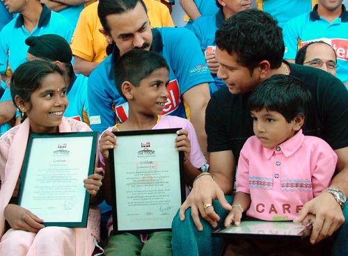 Sachin Tendulkar (right) speaks with children as Bollywood actor Aamir Khan (centre) looks on, in Mumbai