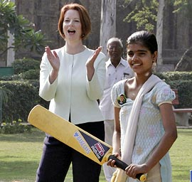 Australian Prime Minister Julia Gillard applauds as girls play cricket during a clinic in New Delhi