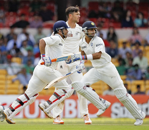 India's captain Mahendra Singh Dhoni (L) and Virat Kohli (R) run between the wickets as New Zealand's James Franklin watches during the second day of their second test cricket match against in Bangalore