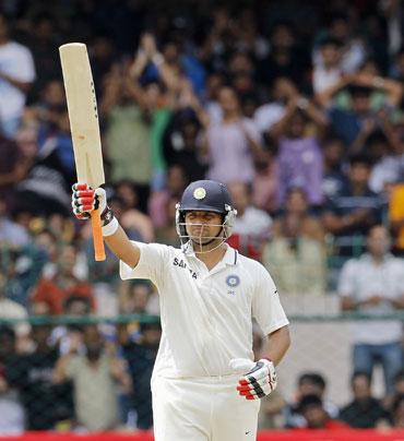 India's Suresh Raina raises his bat to celebrate scoring 50 runs