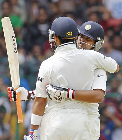 India's Suresh Raina (R) embraces teammate Virat Kohli as he raises his bat to celebrate scoring 50 runs during the second day
