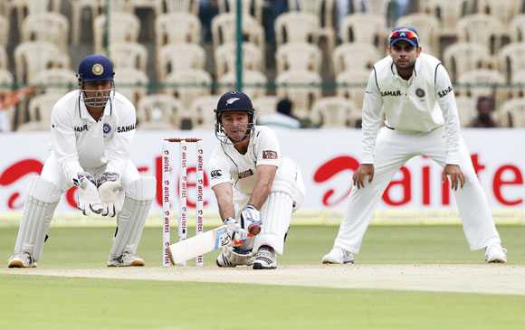 New Zealand's Kruger van Wyk (C) hits a sweep as India's captain Mahendra Singh Dhoni (L) and Virat Kohli watch during the second day of their second test cricket match in Bangalore
