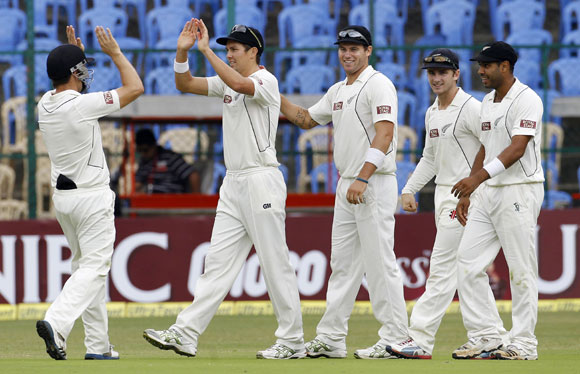 New Zealand's Trent Boult (2nd L) celebrates with teammates after taking a catch off the bowling of teammate Tim Southee to dismiss India's Cheteshwar Pujara