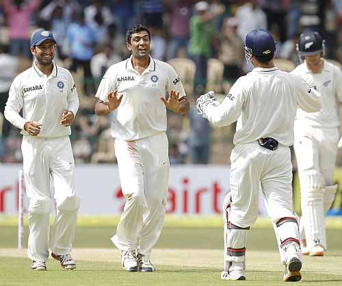 India's R Ashwin celebrates with teammates after dismissing New Zealand's Daniel Flynn during the third day of their second Test match in Bangalore