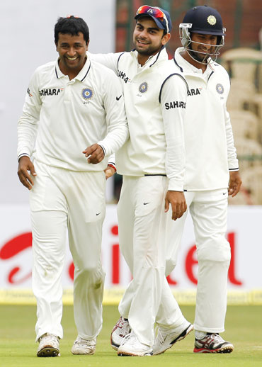 India's Pragyan Ojha (left) celebrates with teammates Virat Kohli (C) and Cheteshwar Pujara