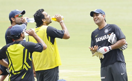 India's captain Mahendra Singh Dhoni (right) while talking to his teammates   during a practice session