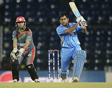 India's Mahendra Singh Dhoni plays a shot as Afghanistan's Karim Sadiq (left) watches