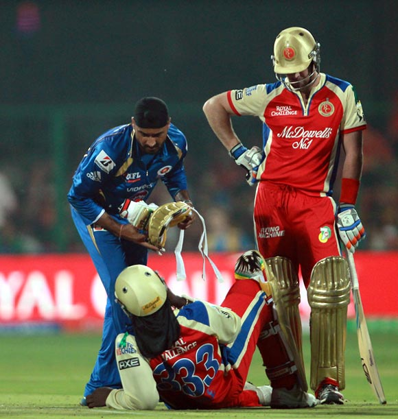 Harbhajan Singh attends to the injured Chris Gayle after the two players collided