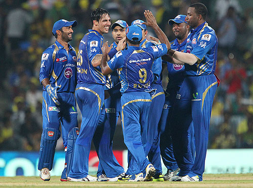 Mitchell Johnson celebrates the wicket of Suresh Raina with his team mates