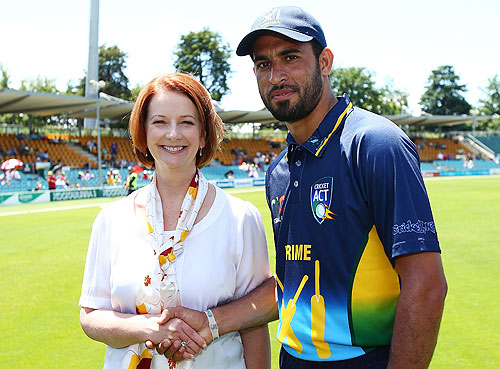 Australian Prime Minister Julia Gillard greats Fawad Ahmed a former Pakistani asylum seeker before the International Tour Match between the Prime Minister's XI and West Indies at Manuka Oval on January 29, 2013 in Canberra, Australia