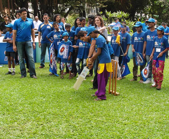 Sachin Tendulkar teaches a young girl to grip the bat