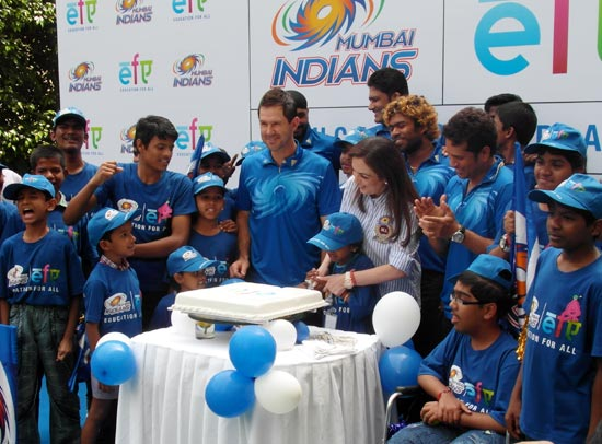 Nita Ambani and a young kid cuts the cake as Lasith Malinga, Sachin Tendulkar and Ricky Ponting look on