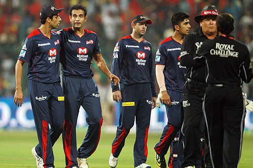 Delhi Daredevils players Ashish Nehra and Irfan Pathan walk off the field with their teammates as the teams go into a Super Over