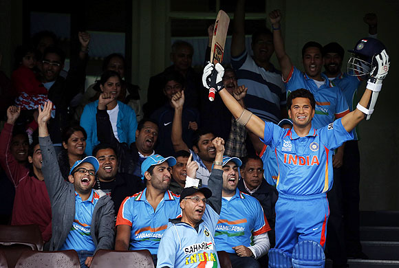 Members of the Indian cricket supporters group known as the 'Swami Army' cheer as they sit next to a wax figure of Indian cricketer Sachin Tendulkar during a promotional event at the Sydney Cricket Ground on Saturday